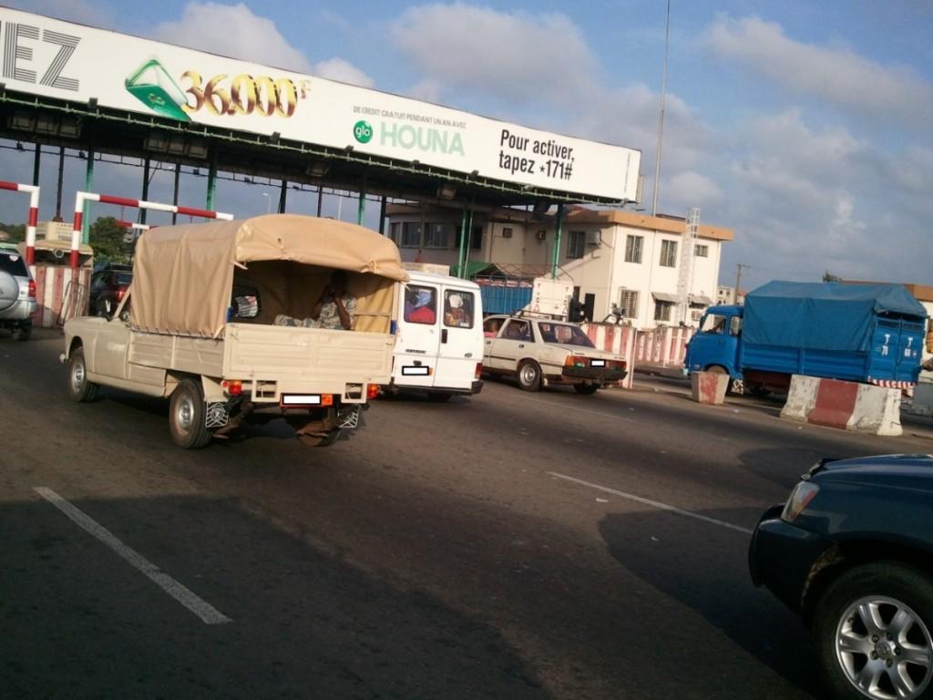 Peugeot 404 bachée et 505 au péage sur l'axe Cotonou- Porto Novo