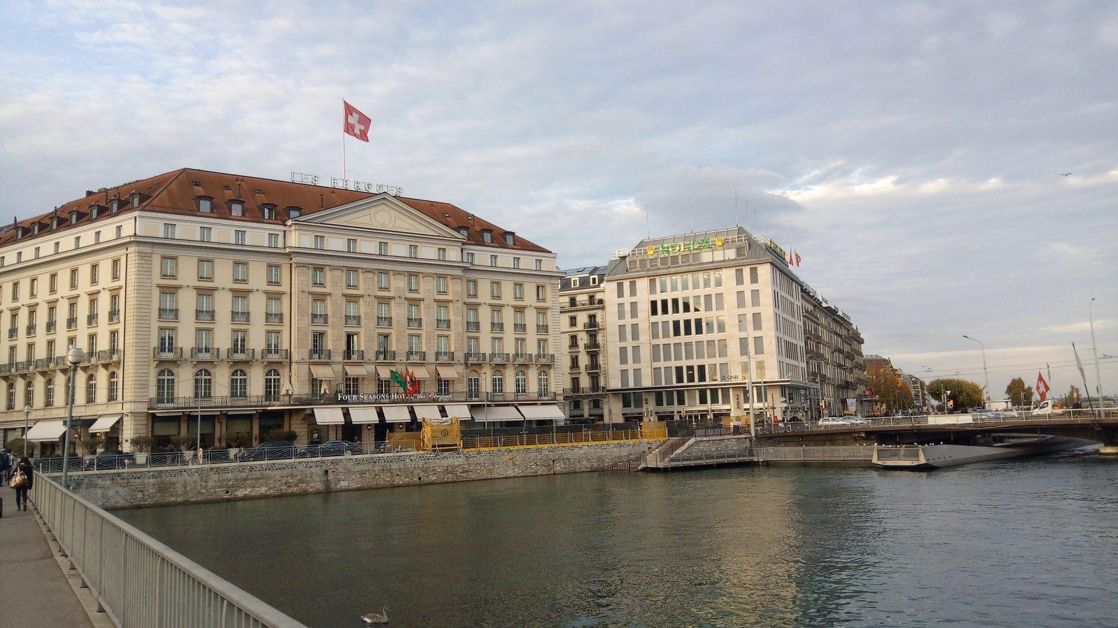 Vue d'un grand hôtel de Genève avec le drapeau suisse et d'un immeuble portant une marque de montre - Photo : Roger Mawulolo
